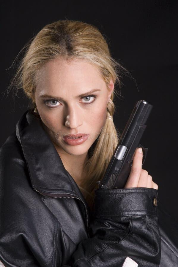 Donna sexy con la pistola in rivestimento di cuoio fotografia stock libera da diritti