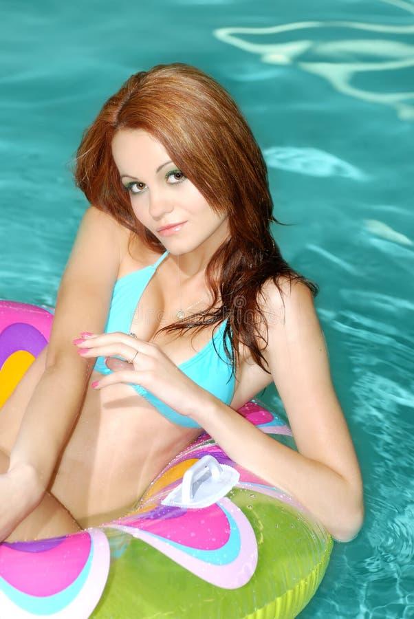 Donna sexy del Brunette che galleggia sul giocattolo del raggruppamento immagine stock