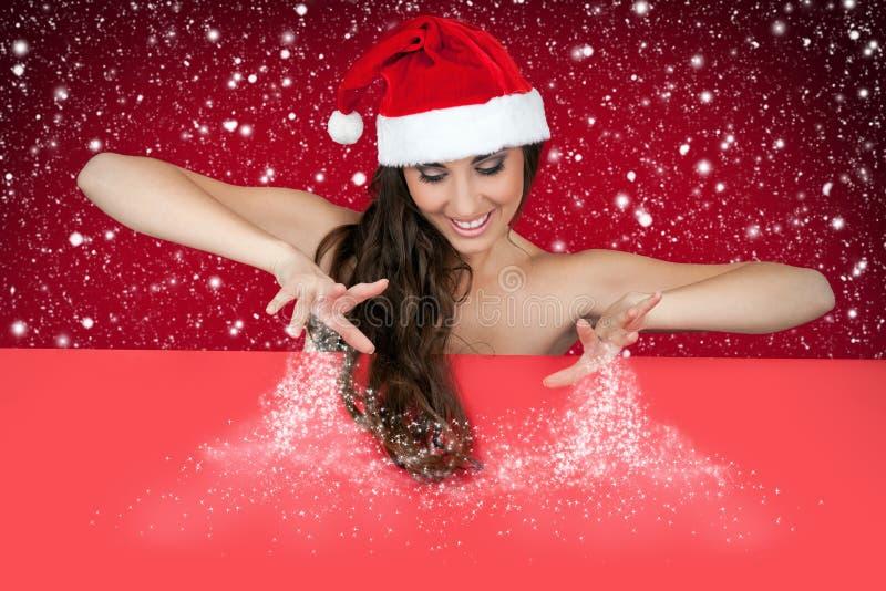 Donna sexy della Santa che spruzza neve a bordo fotografia stock libera da diritti