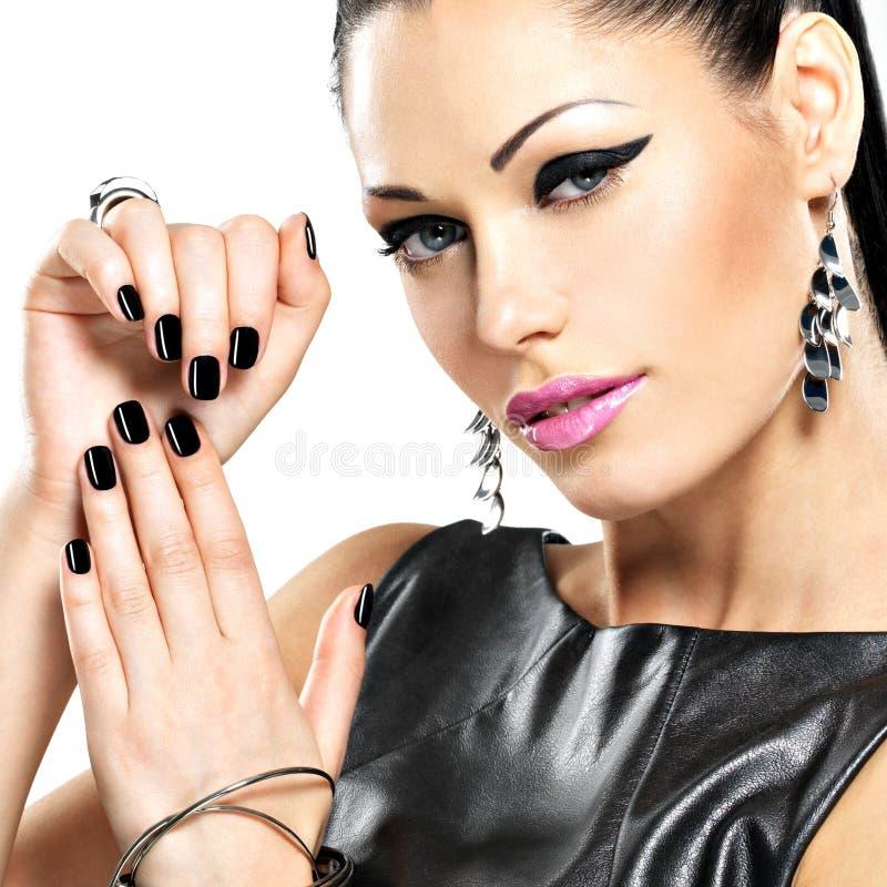 Donna sexy di bello modo con i chiodi neri al fronte grazioso immagini stock libere da diritti