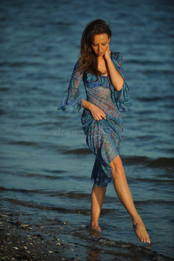 Donna sexy di fascino che posa sulla spiaggia in vestito trasparente floreale immagine stock libera da diritti