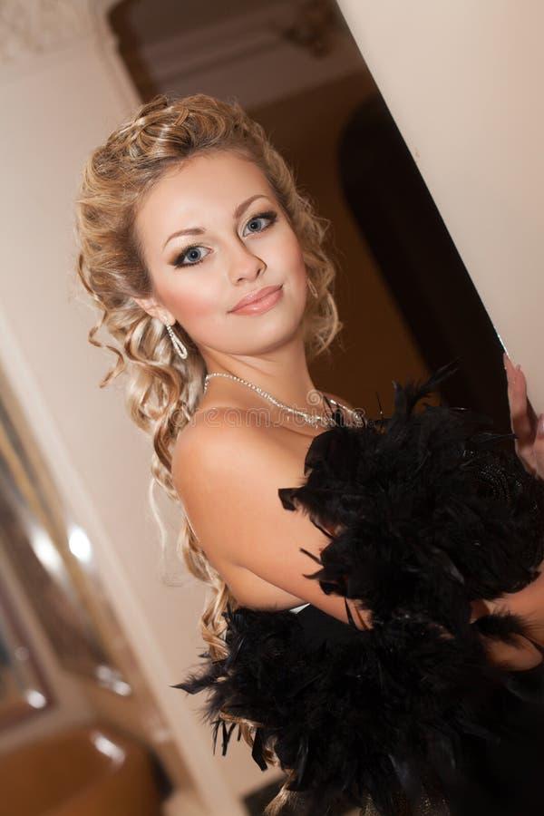 Donna sexy bionda in vestito da sera nell'interno di lusso. Ragazza esile ricca alla moda con l'acconciatura ed il trucco luminoso fotografia stock