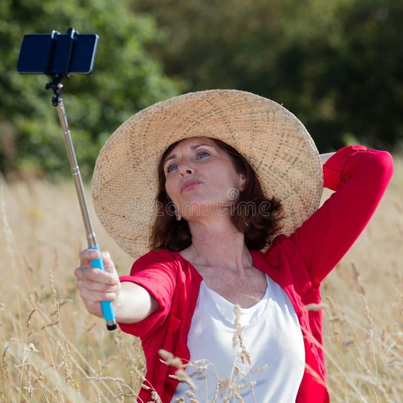Donna sexy di invecchiamento che posa per l'aria aperta selfy e le memorie di vacanza immagine stock
