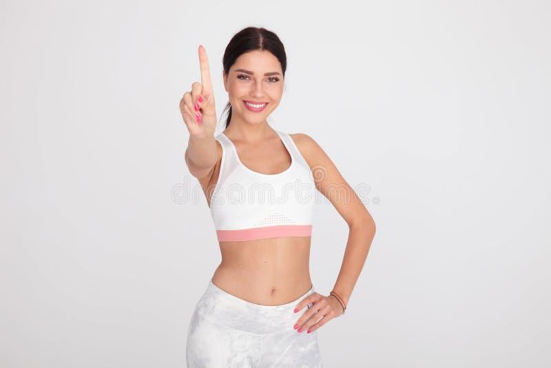 Donna sexy di misura in attrezzatura bianca della palestra che indica dito su fotografia stock