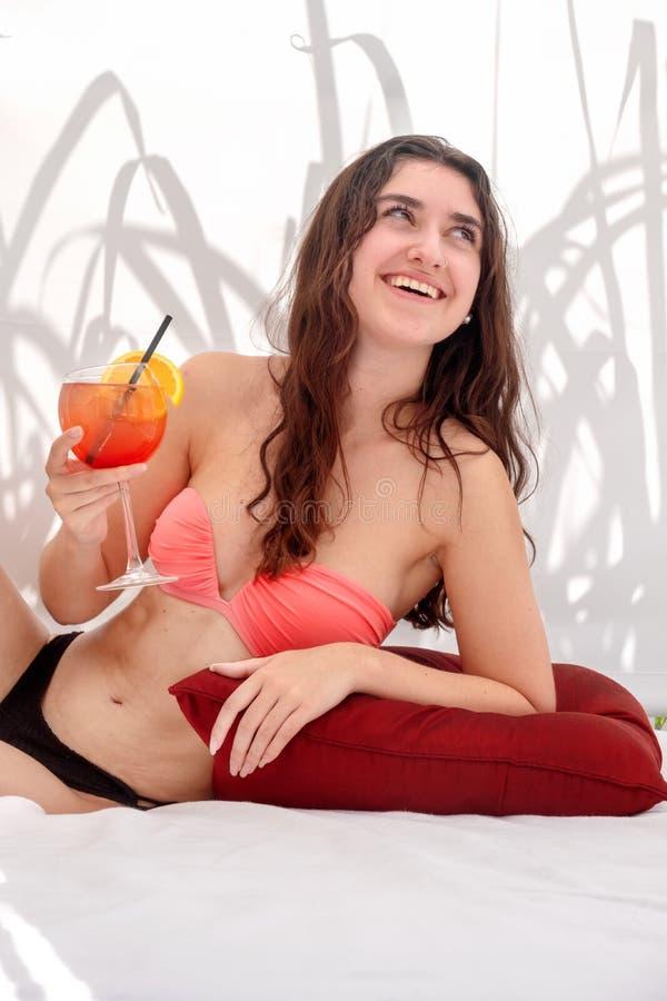 Donna sexy giovane di risata nelle bugie del bikini con un cocktail nel salotto fotografia stock libera da diritti