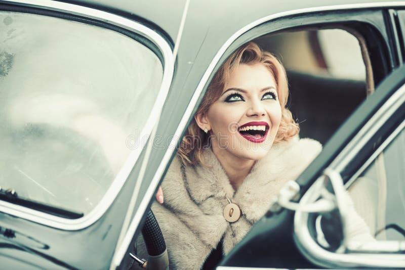 Donna sexy in pelliccia che si siede in retro automobile immagine stock