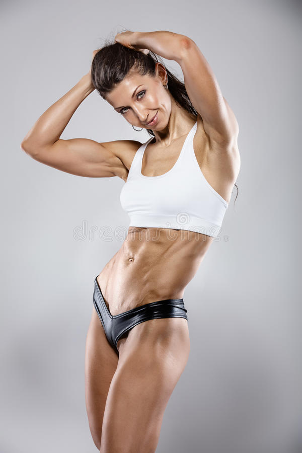 Donna sexy piacevole di forma fisica che mostra i muscoli addominali fotografia stock libera da diritti