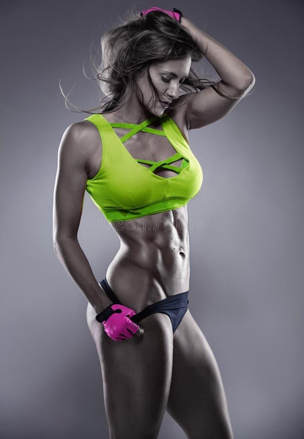 Donna sexy piacevole di forma fisica che mostra i muscoli addominali immagini stock libere da diritti