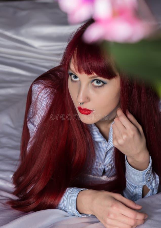 Donna sexy sensuale che riposa su un letto nella camera di albergo Ragazza della testarossa che porta soltanto una camicia fotografia stock