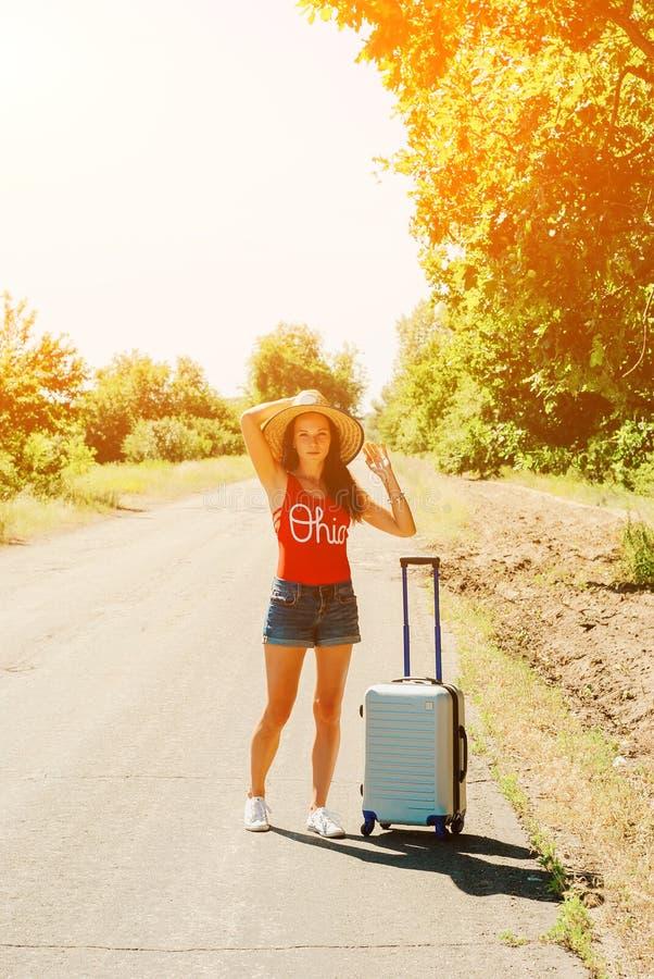 Donna sexy in shorts e cappello dei jeans Ragazza sola con la valigia alla strada campestre immagine stock libera da diritti