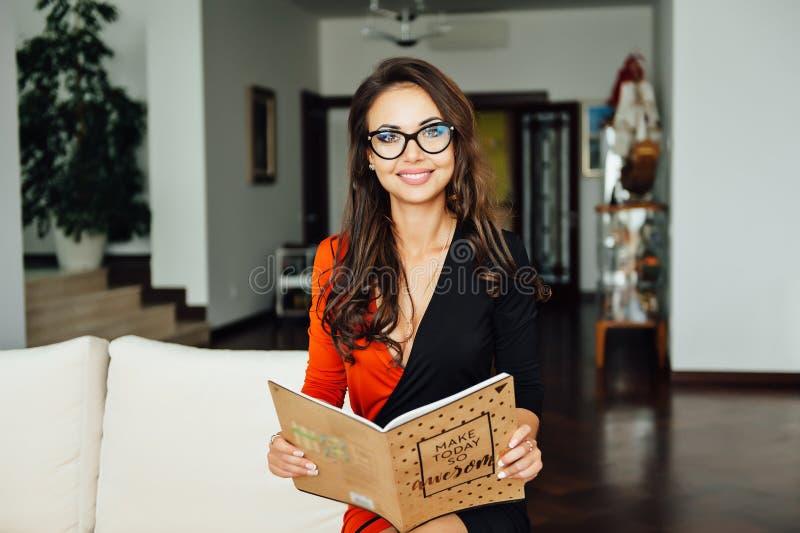 Donna sexy stessa di affari che si siede su un sofà beige nel suo ufficio fotografie stock