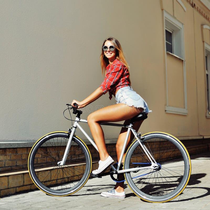 Donna sexy su un ritratto all'aperto di modo della bicicletta fissa dell'ingranaggio fotografia stock libera da diritti