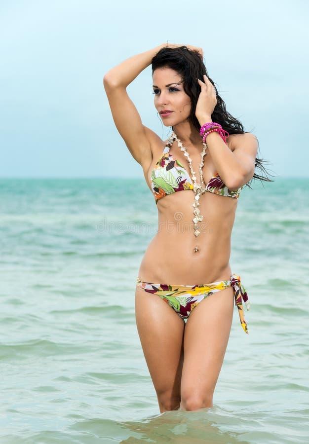 Donna sexy in un ginocchio del bikini in profondità nel mare immagine stock
