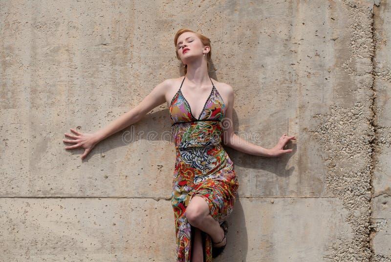 Donna sexy in vestito che si appoggia contro la parete immagine stock libera da diritti