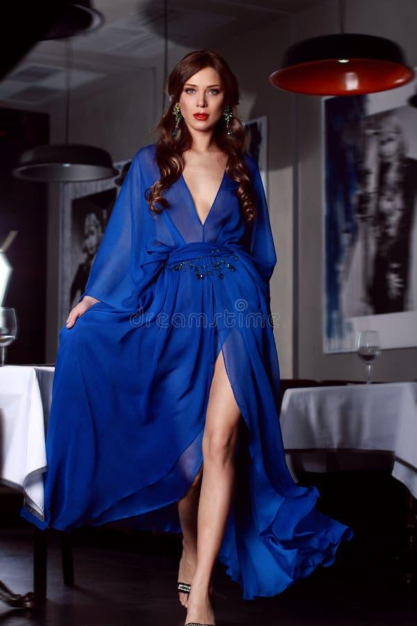 Donna sexy in vestito da sera lungo blu di seta con una fessura fotografie stock libere da diritti