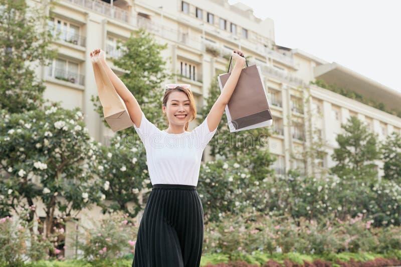 Donna shopaholic beata che balla sulla via con il sorriso immagine stock libera da diritti