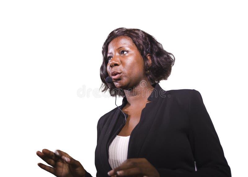 Donna sicura attraente di affari con la cuffia avricolare del microfono che parla al pubblico in sala al seminario corporativo di immagini stock libere da diritti