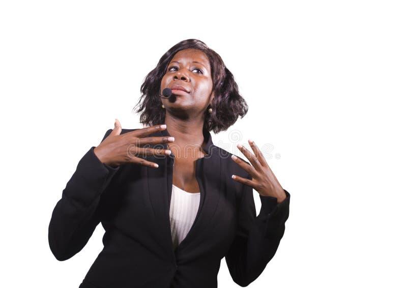 Donna sicura attraente di affari con la cuffia avricolare del microfono che parla al pubblico in sala al seminario corporativo di immagine stock
