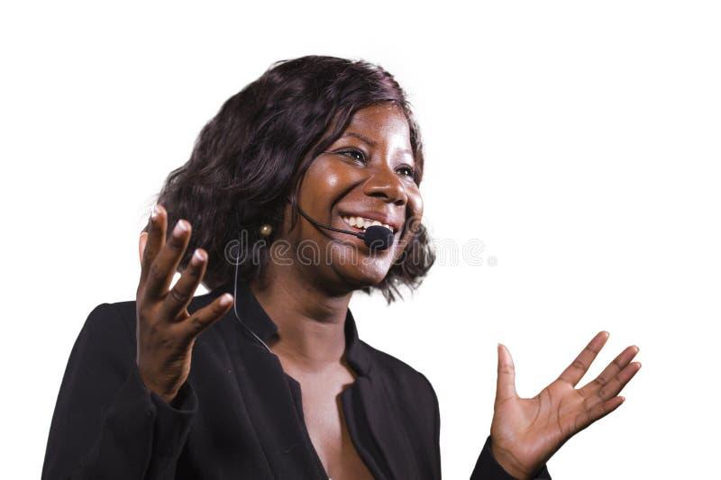 Donna sicura attraente di affari con la cuffia avricolare del microfono che parla al pubblico in sala al seminario corporativo di immagini stock