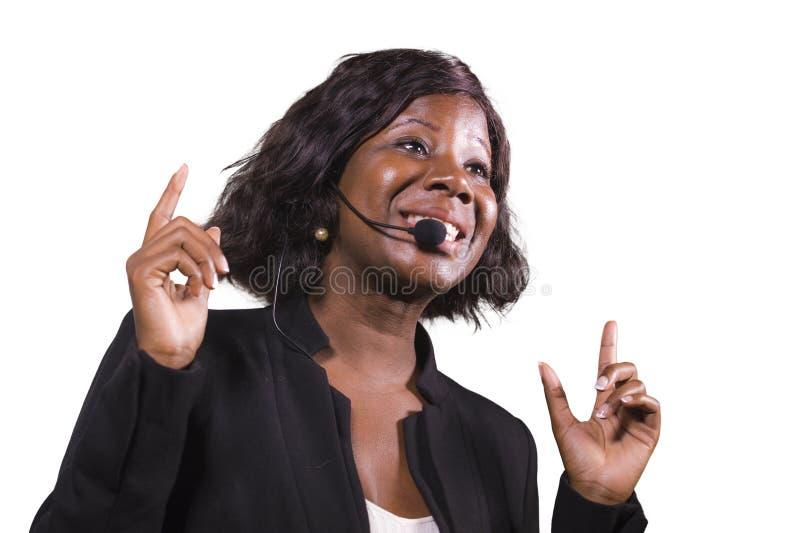 Donna sicura attraente di affari con la cuffia avricolare del microfono che parla al pubblico in sala al seminario corporativo di immagine stock libera da diritti