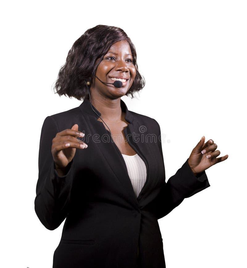 Donna sicura attraente di affari con la cuffia avricolare del microfono che parla al pubblico in sala al seminario corporativo di fotografia stock libera da diritti
