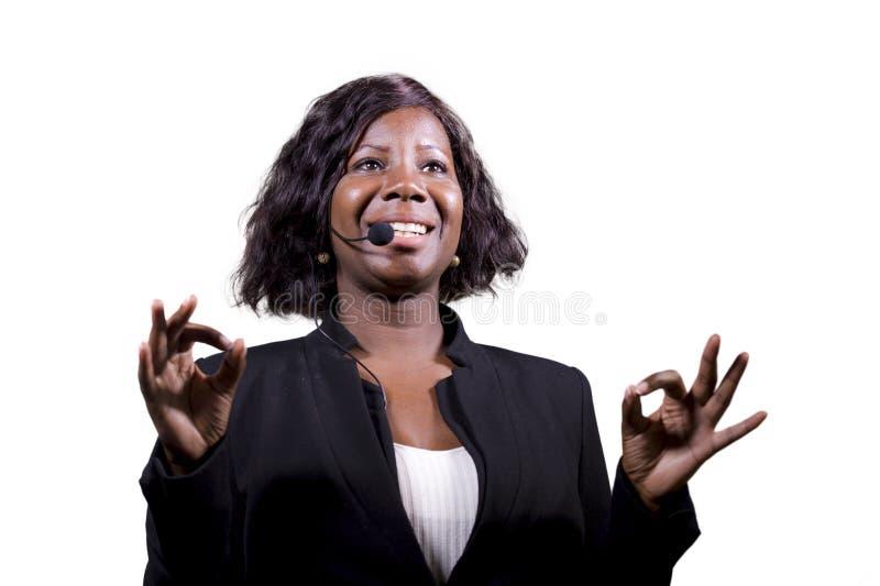 Donna sicura attraente di affari con la cuffia avricolare del microfono che parla al pubblico in sala al seminario corporativo di fotografia stock
