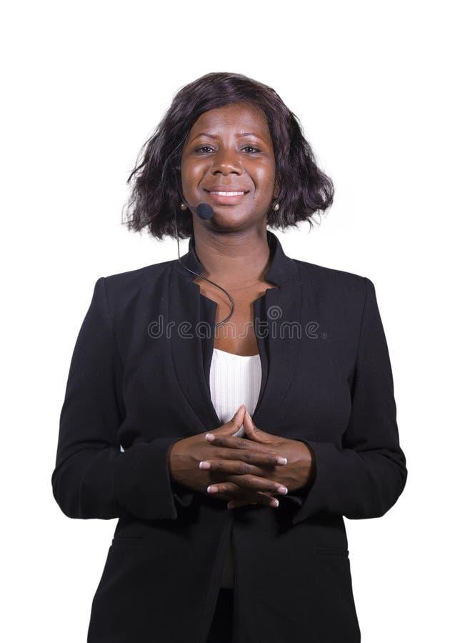 Donna sicura attraente di affari con la cuffia avricolare del microfono che parla al pubblico in sala al seminario corporativo di fotografie stock