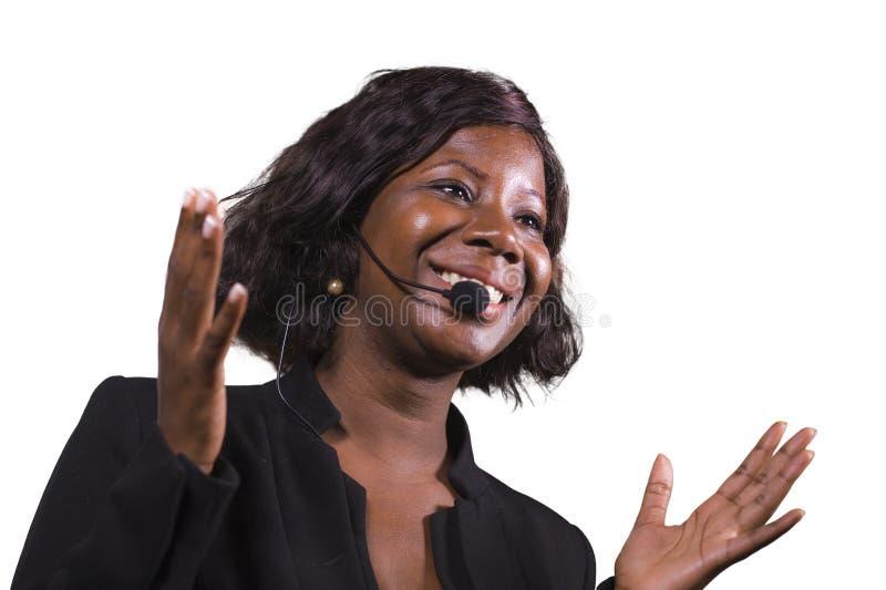 Donna sicura attraente di affari con la cuffia avricolare del microfono che parla al pubblico in sala al seminario corporativo di fotografie stock libere da diritti