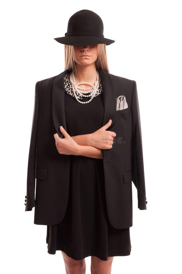 Donna sicura che porta un black hat, un rivestimento e un vestito con la perla immagini stock