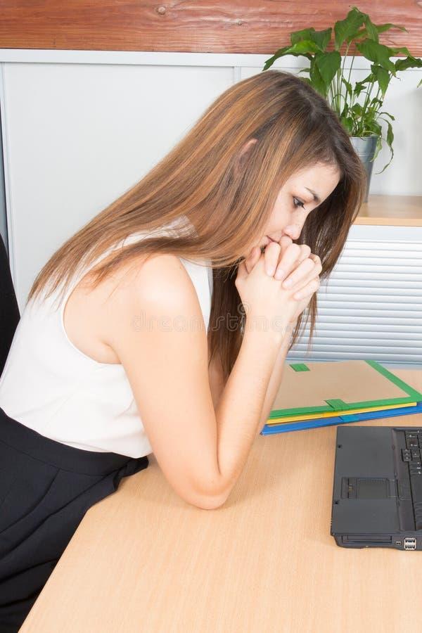 Donna sicura di affari che pensa donna di affari pensierosa che esamina lavorante al suo computer portatile il suo scrittorio fotografie stock