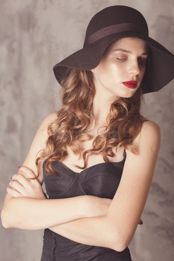 Donna sicura di sé con gambe lunghe in tuta nera e sexy che si presenta in studio con fondo di beton Ragazza in cappello fotografia stock libera da diritti