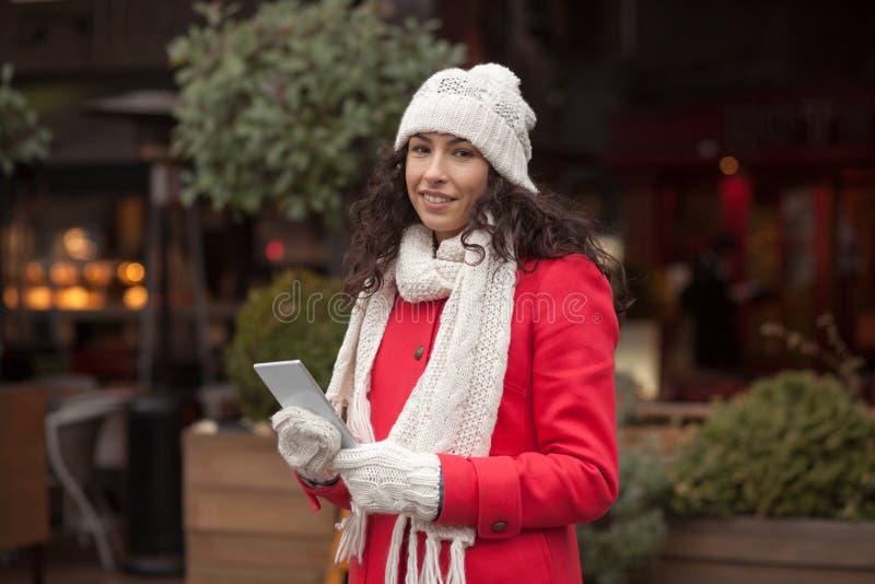 Donna in Smart Phone della tenuta dei guanti della lana fotografia stock