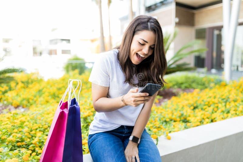 Donna SMS leggente su Smartphone dai sacchetti della spesa fuori del centro commerciale immagine stock