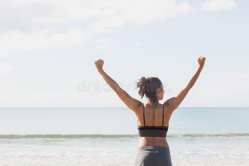 Donna snella adorabile che allunga le sue armi sulla spiaggia fotografie stock libere da diritti