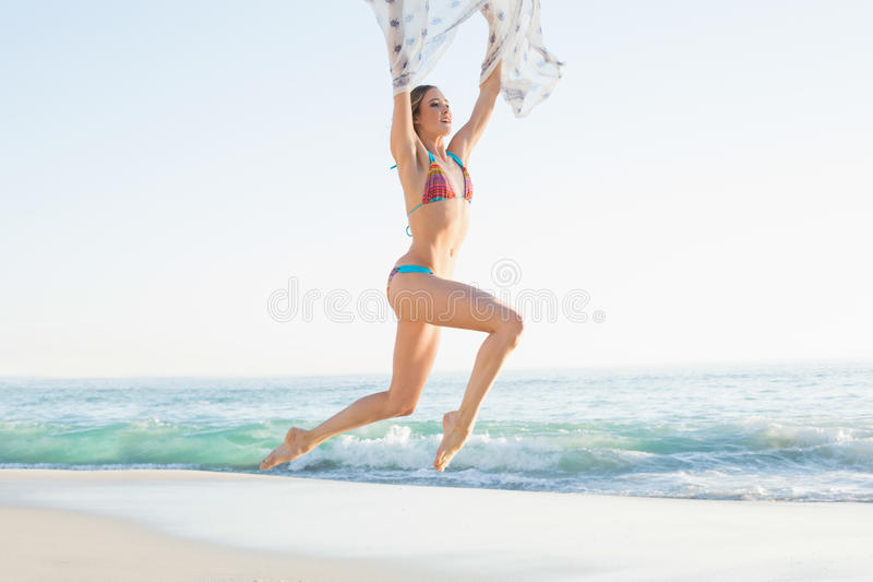 Donna snella allegra che salta nello scialle della tenuta dell'aria fotografie stock