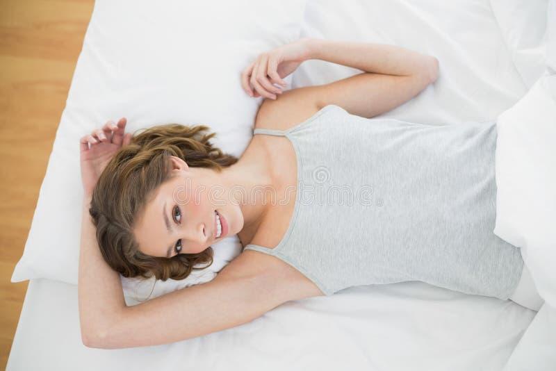 Donna snella attraente che si trova nell'ambito della copertura sul suo letto fotografia stock