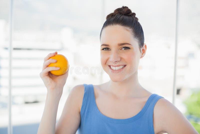 Donna snella sorridente in abiti sportivi che tengono arancia immagini stock libere da diritti