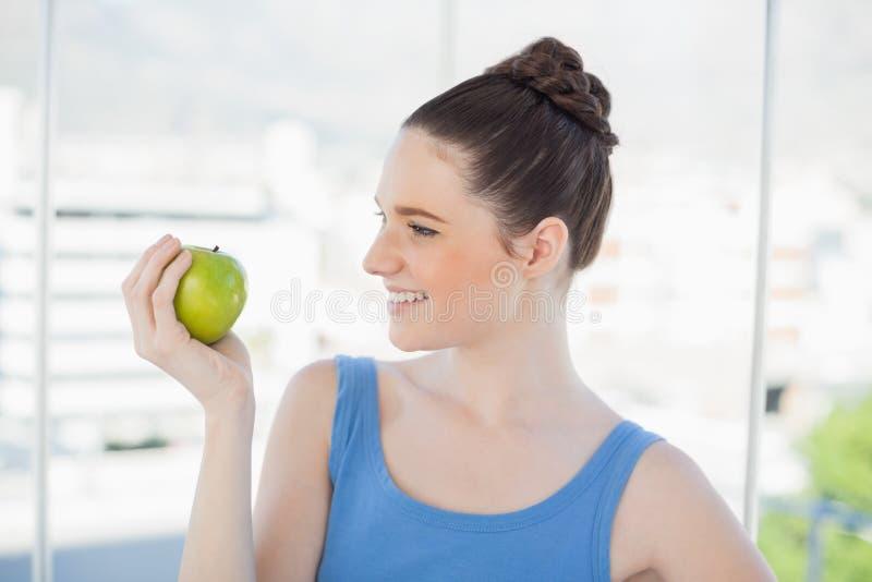 Donna snella sorridente in abiti sportivi che tengono mela verde fotografie stock