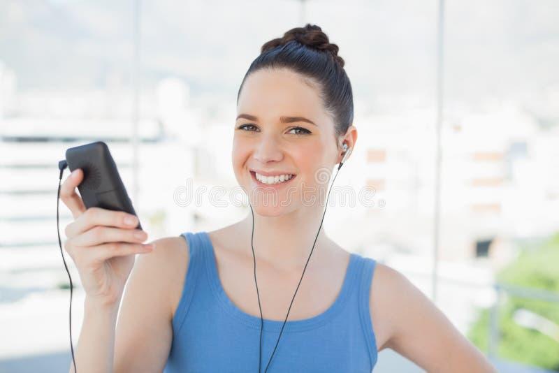 Donna snella sorridente che ascolta la musica immagini stock