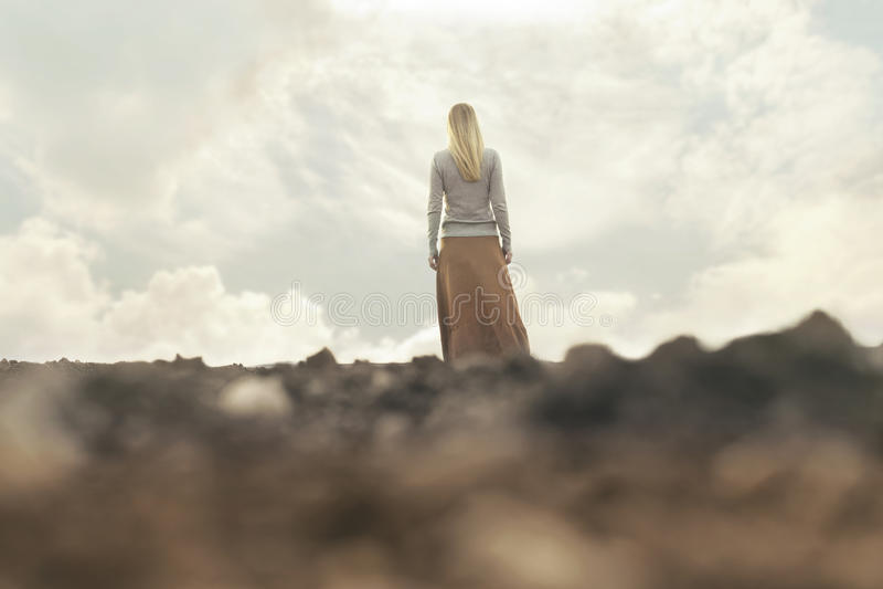 Donna sola che cammina verso l'infinito in un posto surreale immagine stock libera da diritti