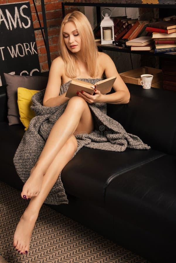 Donna sola che legge un libro mentre sedendosi su uno strato di cuoio avvolto in una coperta di lana fotografie stock