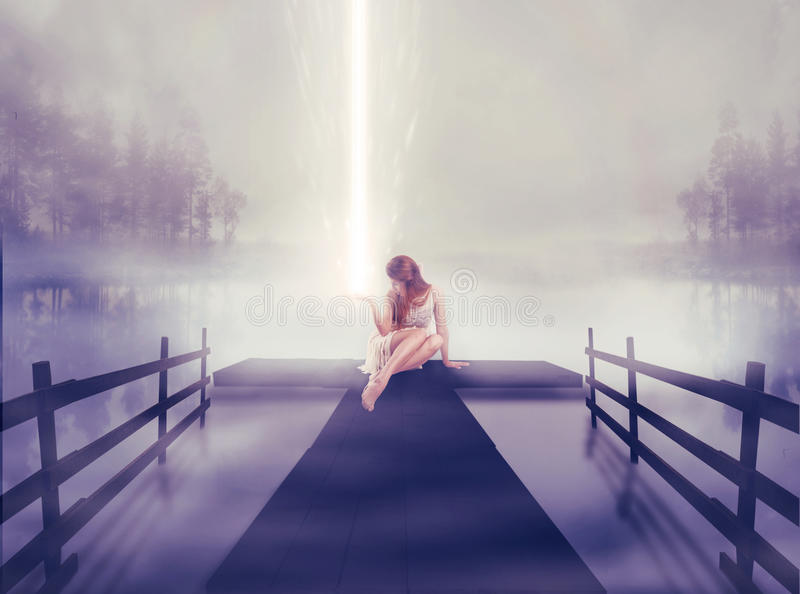 Donna sola che si siede sul pilastro con la palla di ardore leggera in sua mano fotografia stock