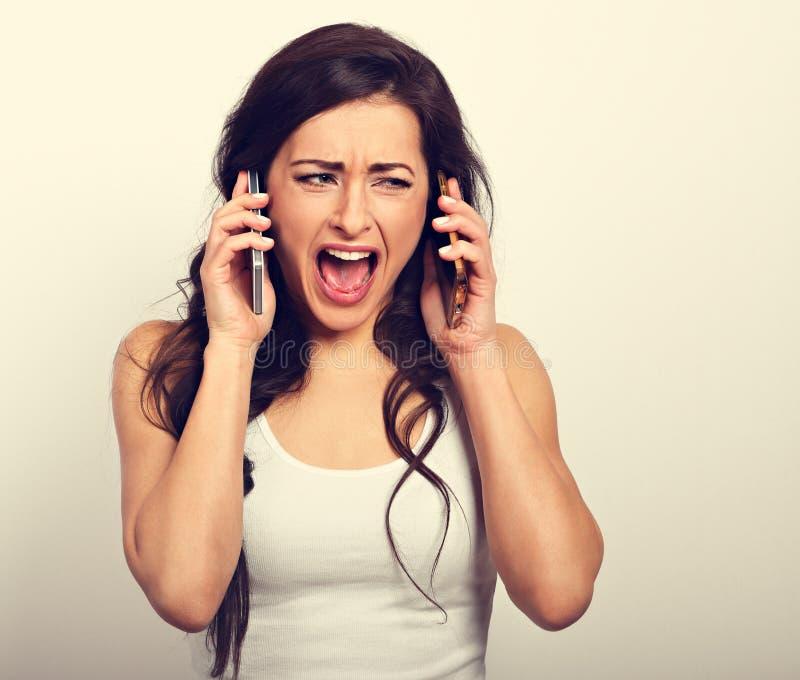 Donna sollecitata arrabbiata infelice che tiene due telefoni cellulari vicino al fotografie stock