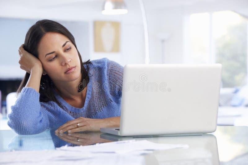 Donna sollecitata che lavora al computer portatile in Ministero degli Interni fotografia stock libera da diritti