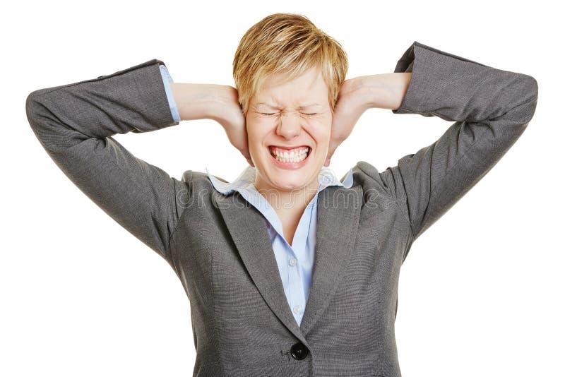 Donna sollecitata di affari che copre le sue orecchie fotografie stock