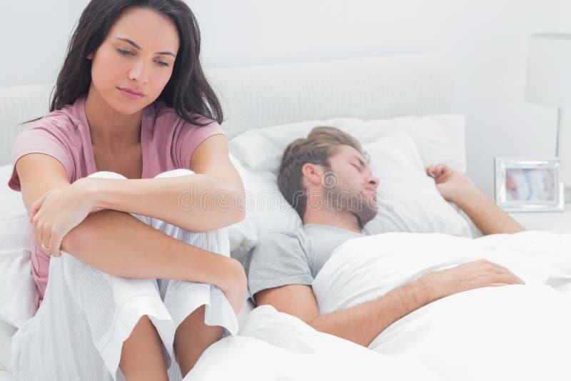 Donna sollecitata nel suo letto immagini stock