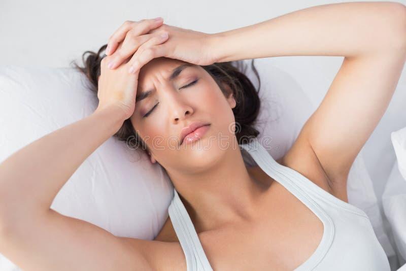 Donna sonnolenta che soffre dall'emicrania a letto fotografia stock libera da diritti
