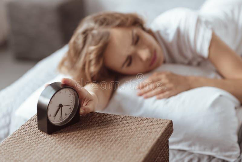Donna sonnolenta che spegne la sua sveglia fotografia stock libera da diritti