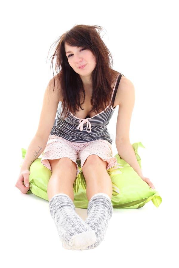 Donna sonnolenta in pigiami che si siedono sul cuscino fotografia stock