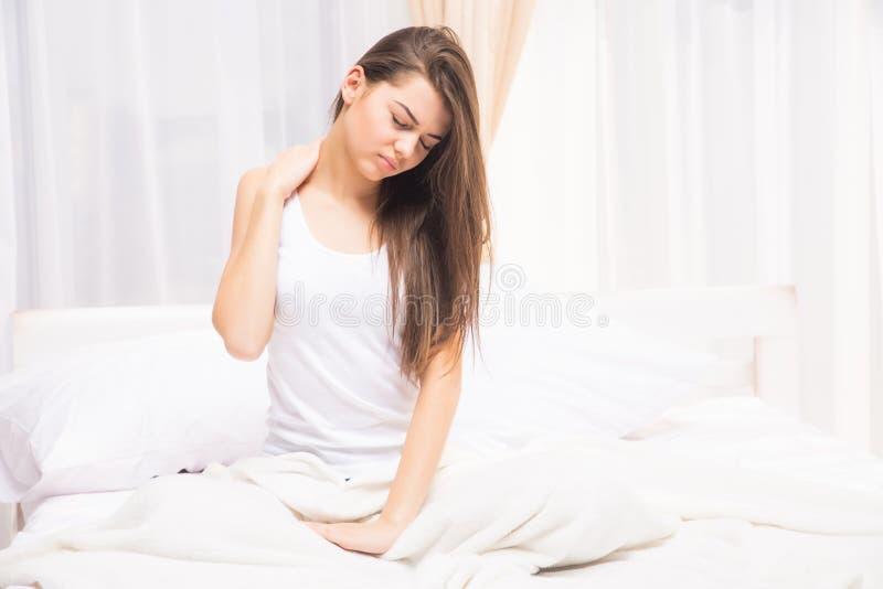 Donna sonnolenta stanca che sveglia e che sbadiglia con un allungamento mentre sedendosi a letto fotografia stock